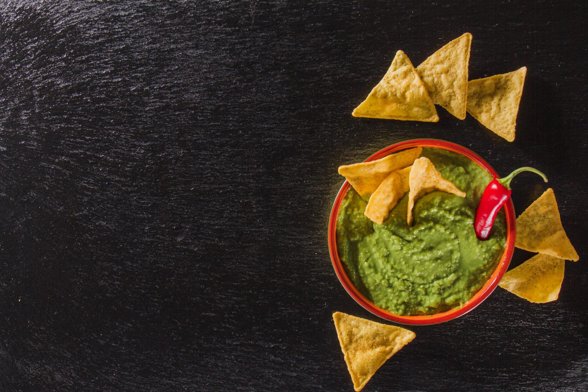 Guacamole com nachos em volta e pimenta no centro
