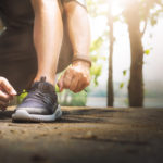 Homem Amarrando o Tenis pronto para correr num parque com pulseira